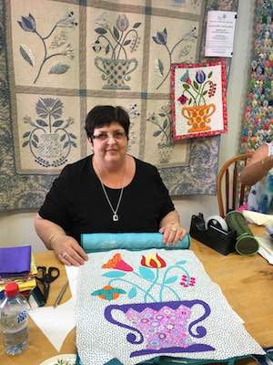 A great photo of Janice in class with Jennifer Corkish. This shot shows the applique block in progress, the sample bright block and larger quilt of Jennifer's design behind her.